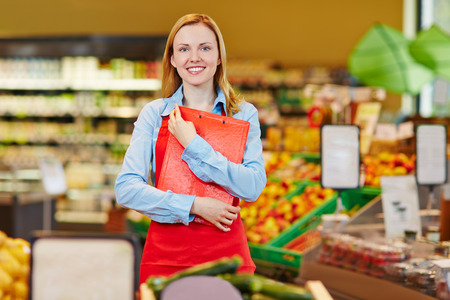 saleswoman: Smiling young saleswoman standing in supermarket with a checklist Stock Photo