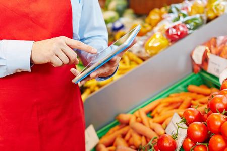 vendedor: Gerente de la tienda haciendo gestión de almacenes con tablet PC en un supermercado