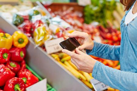 Donna che confronta le informazioni di verdure con il suo smartphone in un supermercato Archivio Fotografico