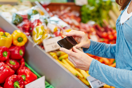 Woman Vergleich von Informationen von Gemüse mit ihrem Smartphone in einem Supermarkt