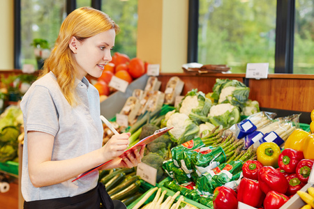 apprenticeship: Woman in supermarket with clipboard making apprenticeship to become salesperson Stock Photo