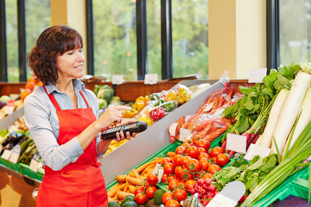 salesperson: Salesperson counting vegetables with mobile data registration terminal for a new delivery in a supermarket