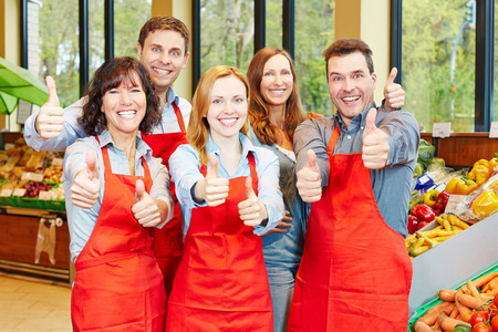 Glückliche Mitarbeiter-Team in einem Supermarkt halten ihre Daumen nach oben