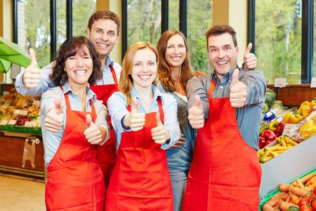 Team di personale felice in un supermercato tenendo le loro pollici in su Archivio Fotografico