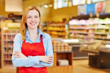 Jonge gelukkige smiiling vrouw doet stage in een supermarkt