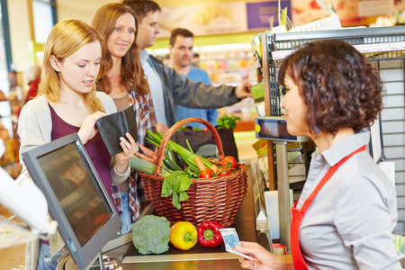 Jeune femme dans la file d'attente de supermarché est manquant l'argent pour le paiement Banque d'images