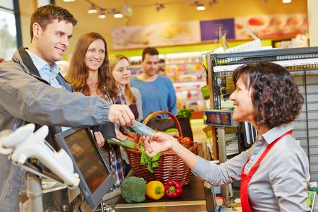 Uomo sorridente pagare generi alimentari al supermercato di checkout con legge finanziaria Euro