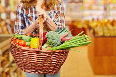 supermercado: Mujer que lleva la cesta llena de verduras en un supermercado Foto de archivo