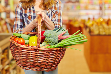 shopping baskets: Woman carrying shopping basket full of vegetables in a supermarket Stock Photo