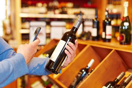 Mano con lo smartphone bottiglia di vino di scansione in un supermercato per il confronto prezzi