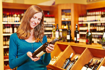 wine trade: Elderly smiling woman buying bottle of red wine in a supermarket