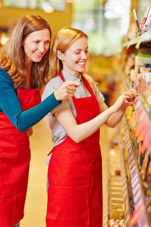 put away: Storewoman in apprenticeship in supermarket getting help from elderly salesperson