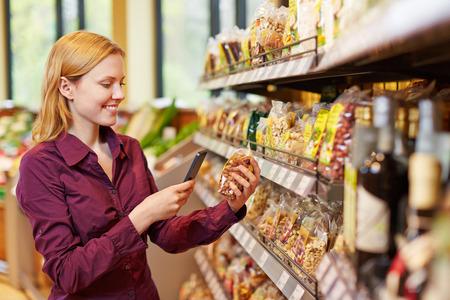 Jeune code à barres de balayage de femme de sac de noix dans un supermarché avec son téléphone intelligent