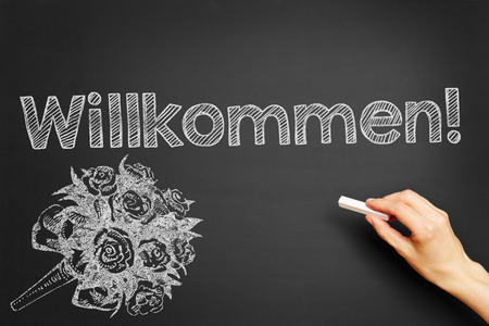 cordiality: Hand writes in German Willkommen! (Welcome!) on blackboard Stock Photo