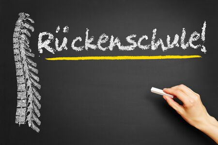 dorsalgia: Hand writing the German word Rueckenschule (back therapy) on a blackboard Stock Photo