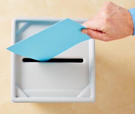 Hand zetten stemming in de stembus tijdens de verkiezingen