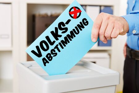 democracia: Mano con la papeleta electoral en la caja con la palabra alemana Volksabstimmung (referéndum)