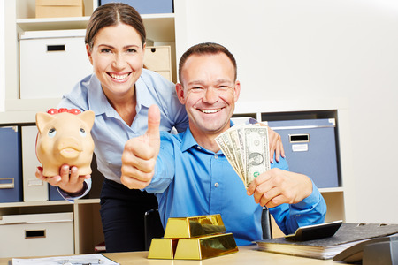 woman bar: Happy couple with Dollar money and gold and piggy bank holding thumbs up Stock Photo