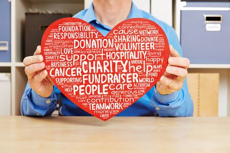 Man holding big red heart with charity and fundraiser tag cloud against cancer