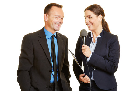 pr: Press officer of a company giving interview to journalist with a microphone Stock Photo