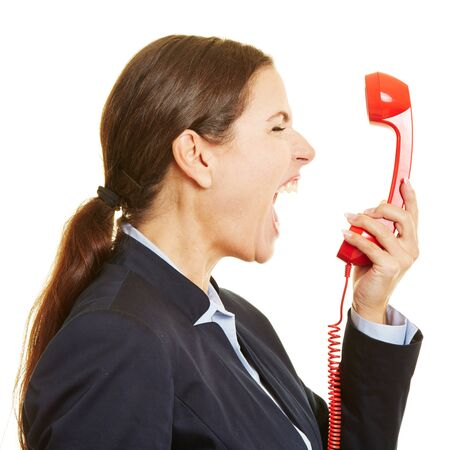 loudly: Angry businesswoman screaming loudly into a red phone