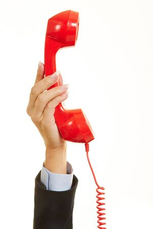 cry for help: Hand of a woman holding a red phone for emergency call Stock Photo