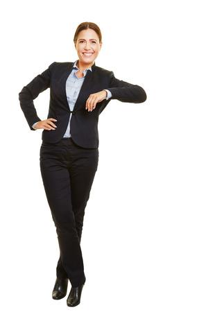 Sorridente isolato donna d'affari di tutto il corpo appoggiato casuale su un oggetto immaginario
