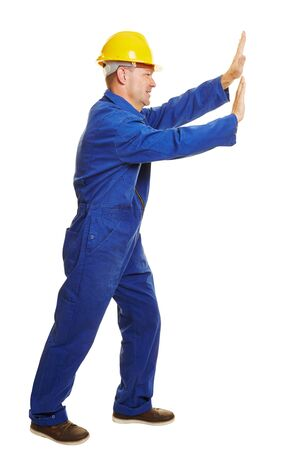 boiler suit: Isolated full body construction worker in boiler suit pushing an imaginary wall Stock Photo