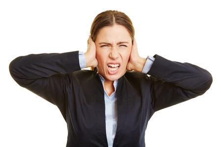 dolor de oido: Mujer de negocios enojada muecas y tapándose los oídos con las manos