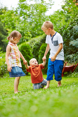 help: Two helpful children helping baby learning to walk in a garden in summer Stock Photo