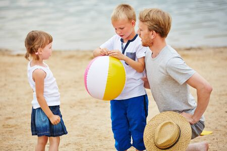 child ball: Father playing with two children and beach ball on beach in summer
