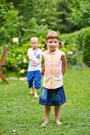 string together: Two children playing together in a garden and pulling a string