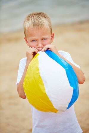 inflating: Boy in summer inflating a beach ball with his mouth
