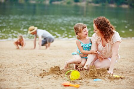 sandpit: Mother and daughter building a sand castle together on a beach