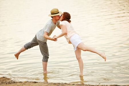 kissing mouth: Couple in love kissing in water of lake in summer Stock Photo