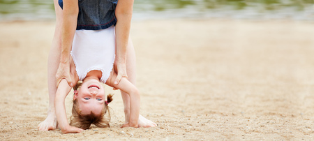 beach panorama: Happy girl doing handstand on beach with help of her mother Stock Photo