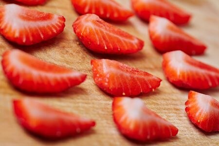 quartered: Quarted fresh strawberries assorted on a wooden board Stock Photo