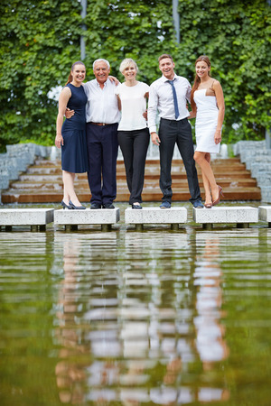 competent: Portrait of competent business team outdoors near a lake Stock Photo
