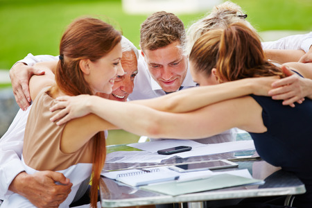 team spirit: Business people hugging for team spirit in a meeting at a table