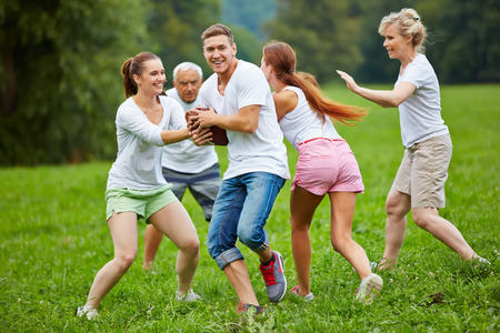 football play: Smiling family playing american football on a meadow in their garden Stock Photo