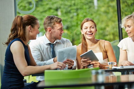 Young businesswoman laughing in business team meeting