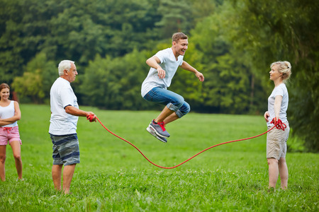 Man rope skipping with jumping rope with his family in nature Stock Photo