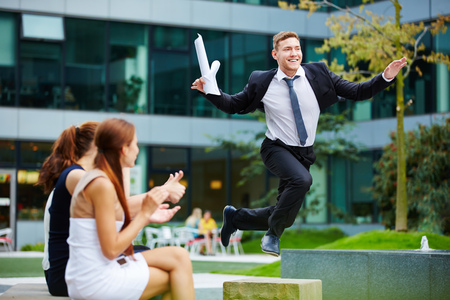 joy: Brave businessman jumping over obstacle in front of his team members