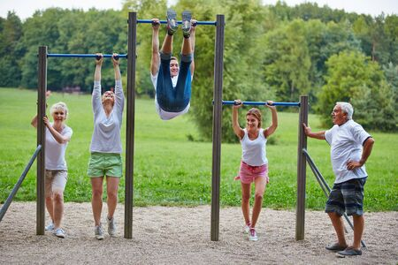 family exercise: Family doing fitness training together in park at horizontal bars