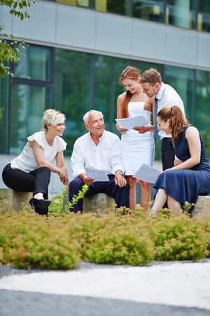 team working: Group of business people having a meeting outdoors in summer Stock Photo