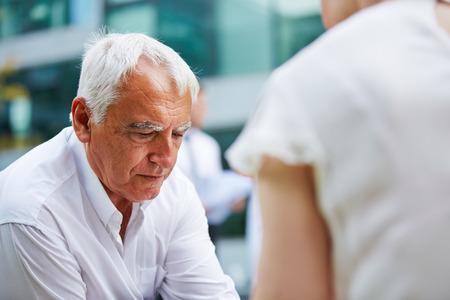 trabajando en casa: Pensativo hombre de negocios mayor que se sienta preocupado al aire libre Foto de archivo