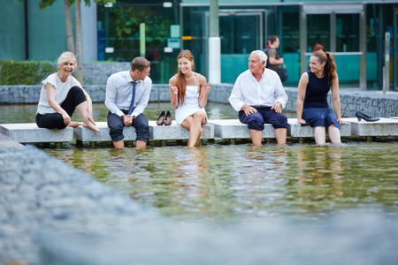 break: Happy business people talking during break in summer with their feet in water