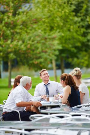 夏のレストランで屋外会議を有するビジネス チーム
