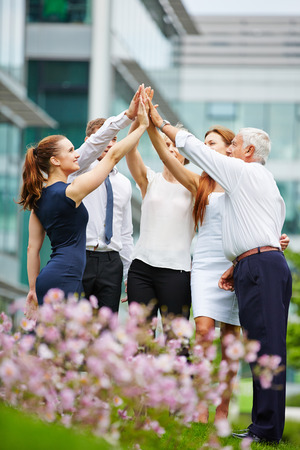 Gruppe Geschäftsleute geben high Five im Freien vor dem Büro