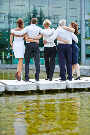 team from behind: Group of business people looking together to their office building Stock Photo